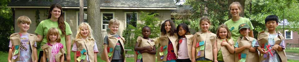 A group of children attending a camp, standing outdoors in a row, with two of our educators
